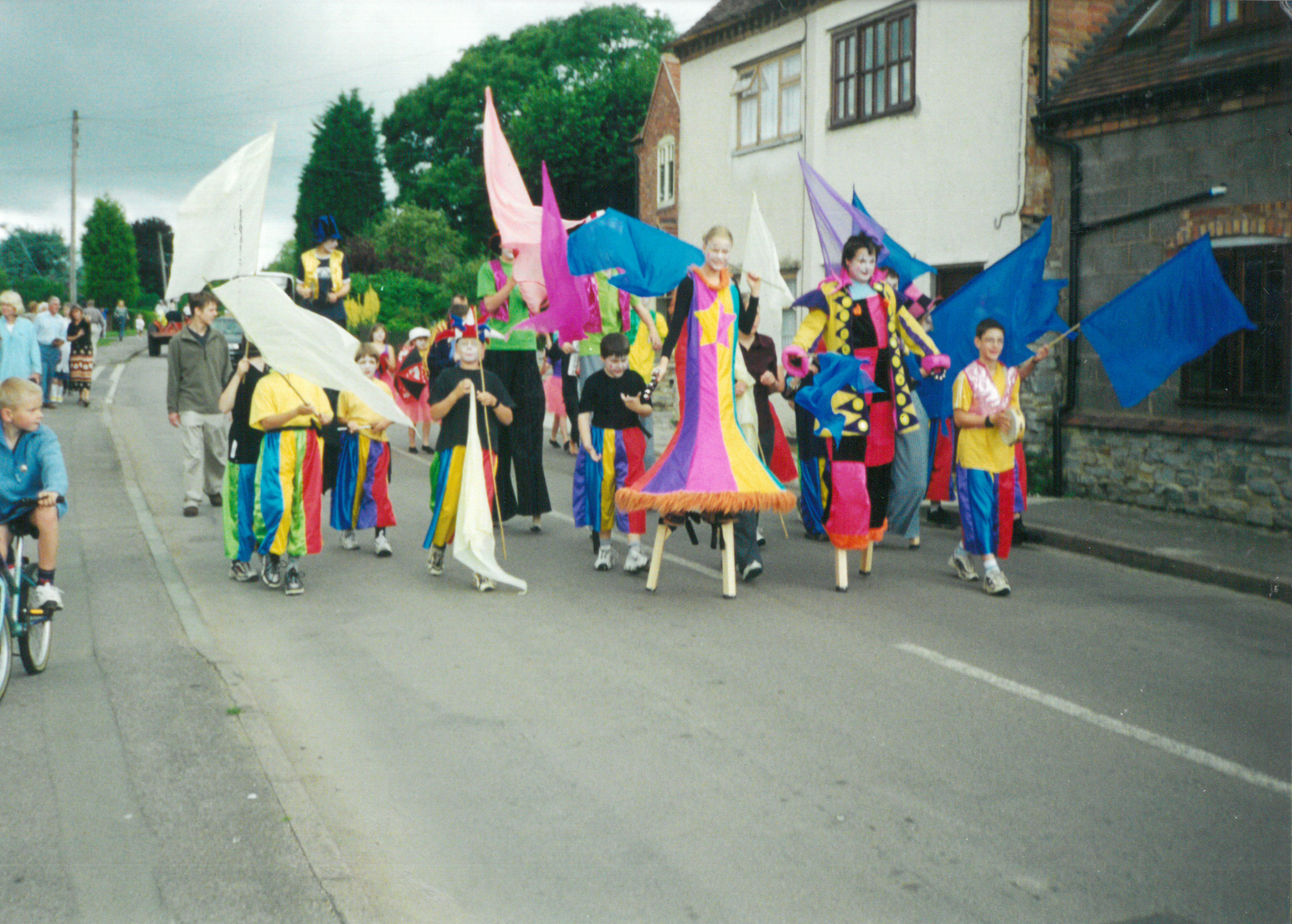 A colourful procession of people on stilts and with flags  down a street.