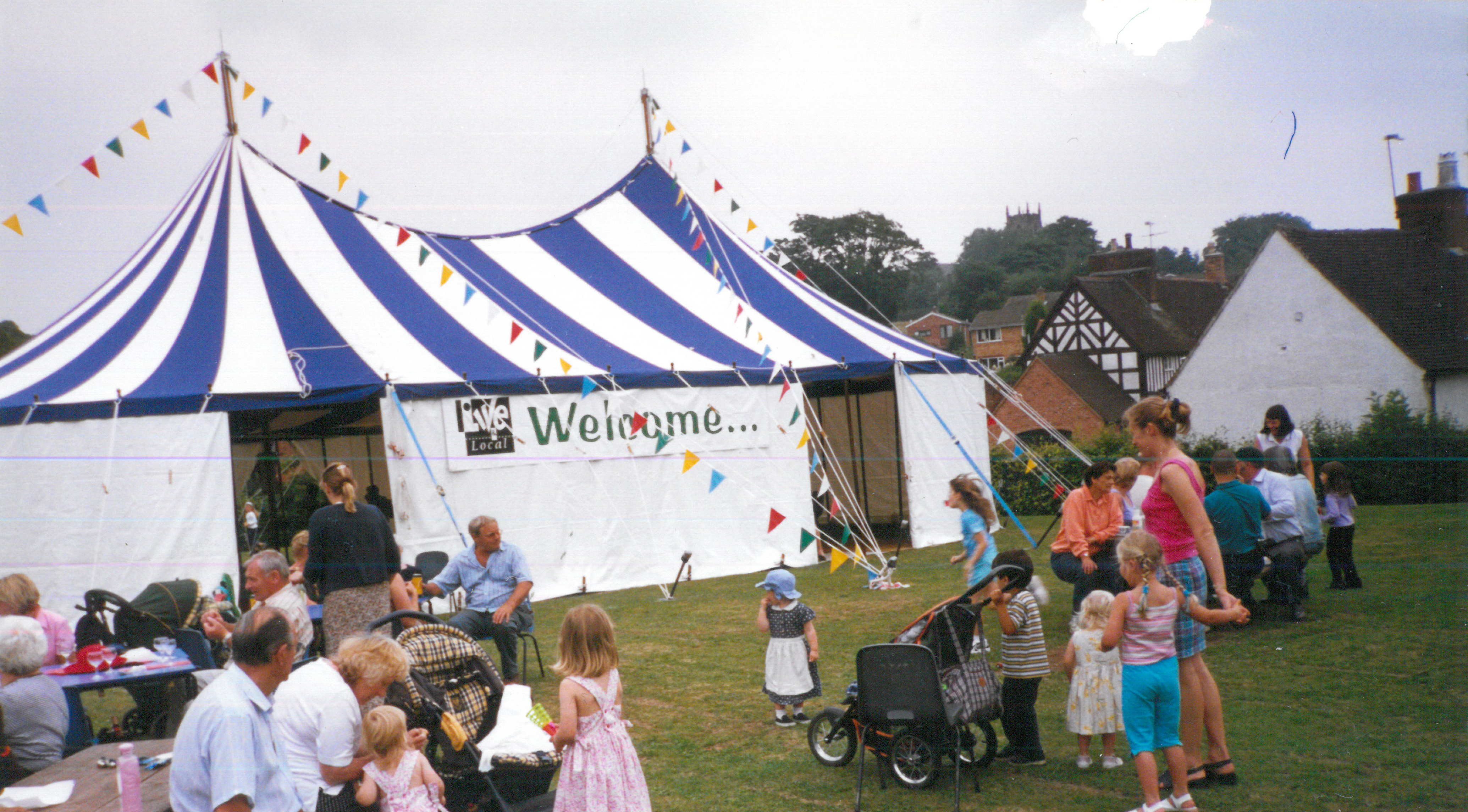 A blue and white high top tent with children outside