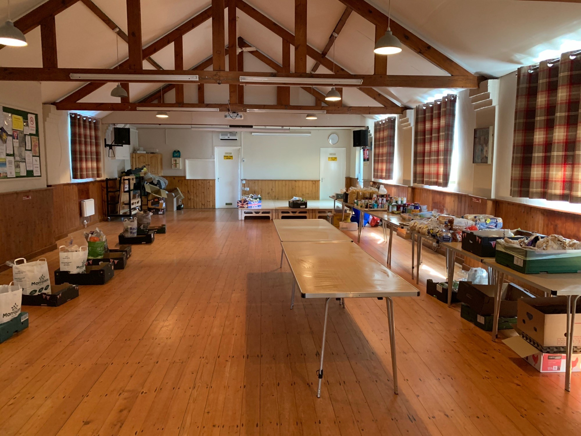 Inside Long Marston Village Hall. Long tables and shopping bags set out to be a food bank