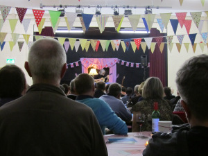 An audience watching a guitarist in a village hall with colourful bunting.