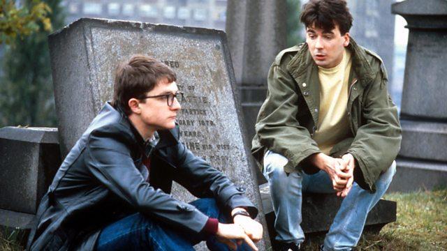 Two teenagers sitting on gravestones talking