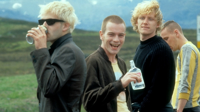 Still from Trainspotting. A group of four: two drinking and Ewan McGregor smiling.