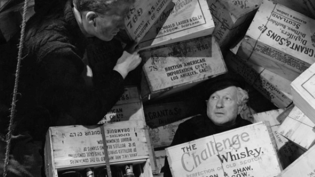 Two men in amongst whisky boxes. From Whisky Galore